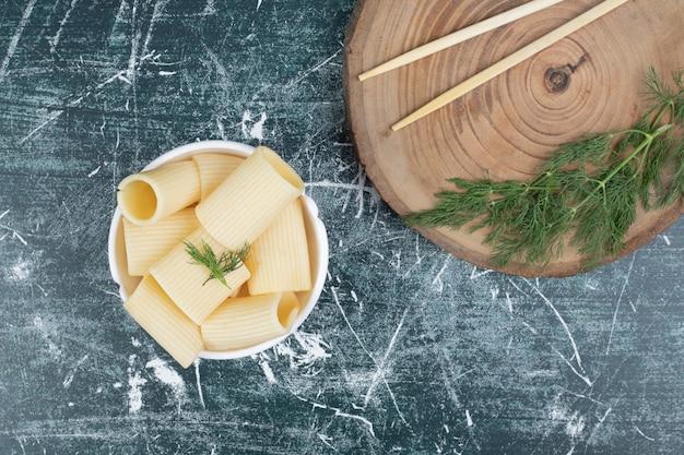 Massa cozida em uma tigela branca com pauzinhos e coentro. foto de alta qualidade
