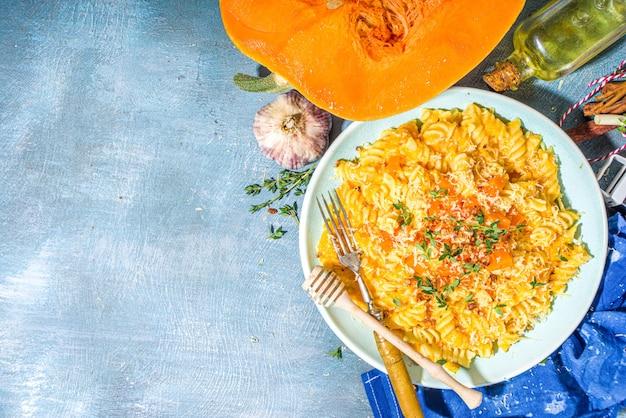 Massa cremosa e cremosa de abóbora vegana, fusilli com molho de abóbora, queijo e tomilho, no fundo da mesa de concreto azul cópia espaço