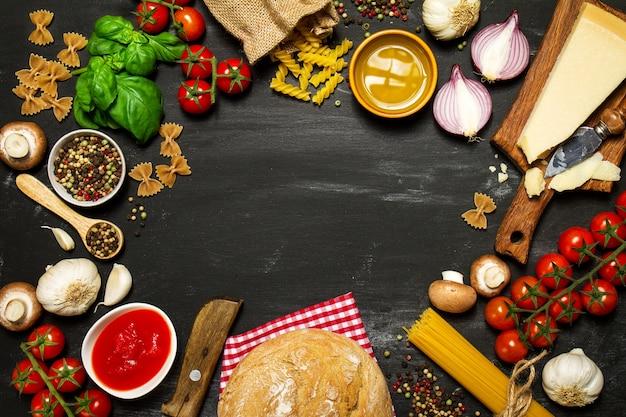 Massa crua com tomates e queijo em uma tabela preta que fazem um círculo