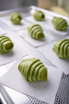 Massa crua de croissant de chá verde com recheio de chá verde antes de assar na bandeja.