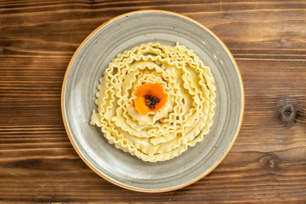 Massa crua de vista superior massa projetada dentro de um prato sobre fundo de madeira marrom