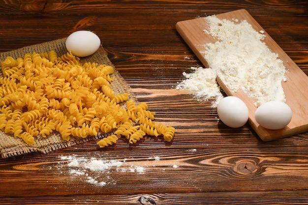 Massa crua e ingredientes para massas em fundo de madeira.