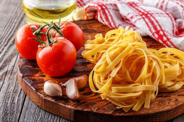 Massa crua e tomate em uma tábua