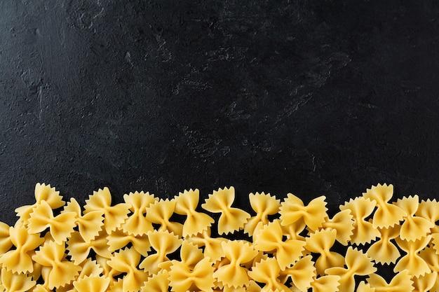 Massa crua farfalle na mesa de concreto preta. conceito de cozinha. vista superior com espaço de cópia.