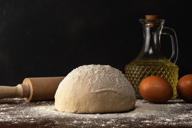 Massa crua fresca para pão ou pizza com ovos e óleo em uma mesa de madeira escura