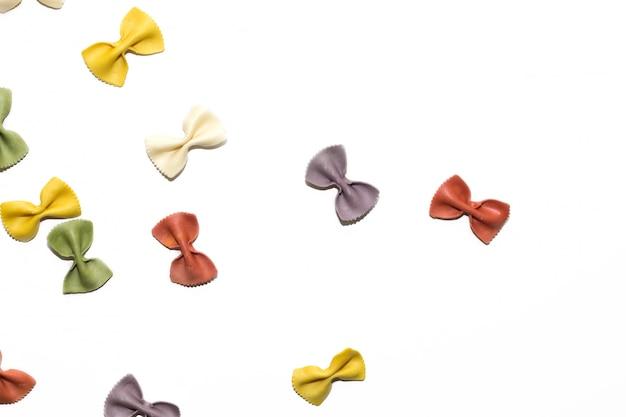 Massa crua italiana do farfalle colorido no fundo branco com espaço da cópia.