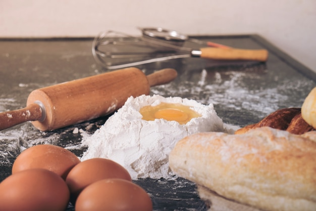 Massa crua para pão com ingredientes em fundo preto