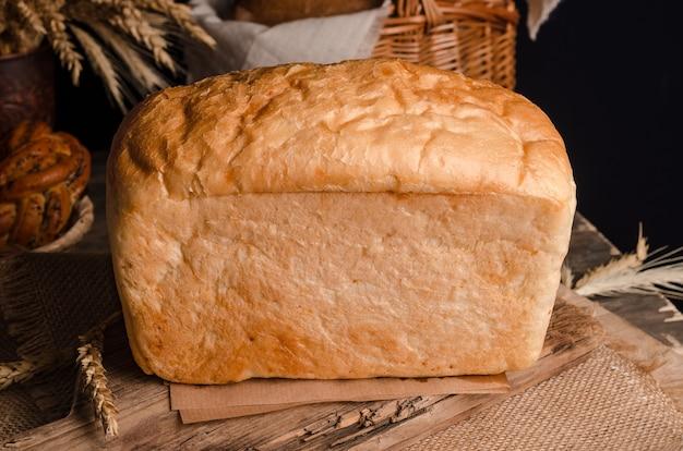 Massa culinária fresca apetitosa - pão branco com fundo de madeira