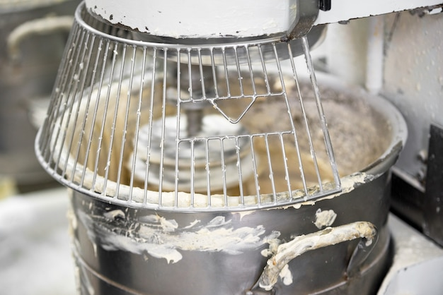 Massa de amasso na máquina do misturador de massa da padaria.