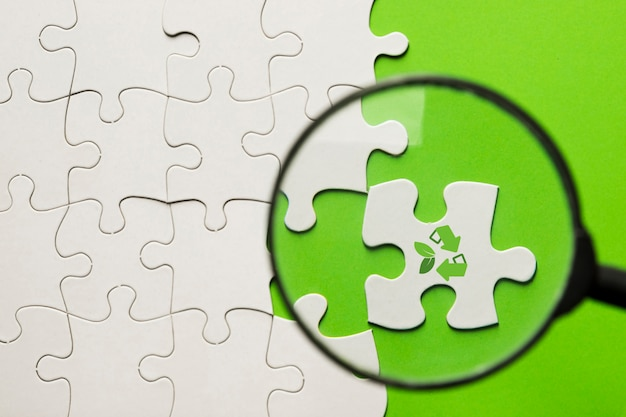 Massa de ampliação em quebra-cabeça branca com o ícone de reciclagem sobre a superfície verde