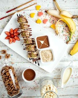 Massa de banana coberta com calda de chocolate e pistache ralado