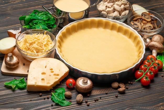Massa de biscoito amanteigado para assar torta de quiche na forma e ingredientes de cozimento