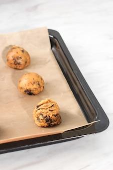 Massa de biscoito cru isolada no fundo branco com colher de sorvete para medir no fundo. home baker passo a passo fazendo biscoitos de chocolate.