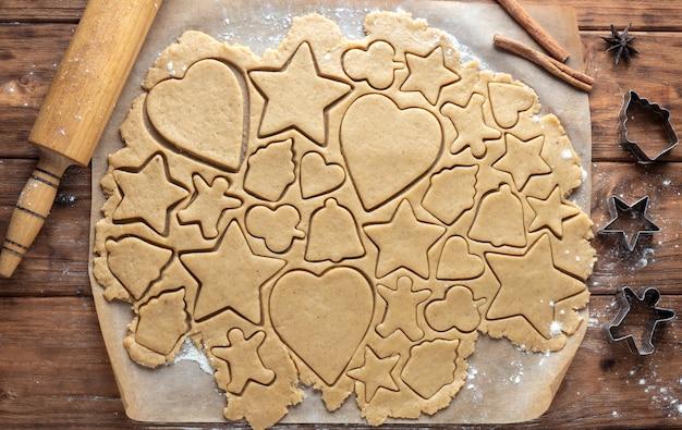 Massa de biscoito de gengibre com figuras cortadas em fundo de madeira