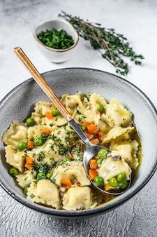 Massa de bolinhos de sopa de ravioli em uma tigela com verduras