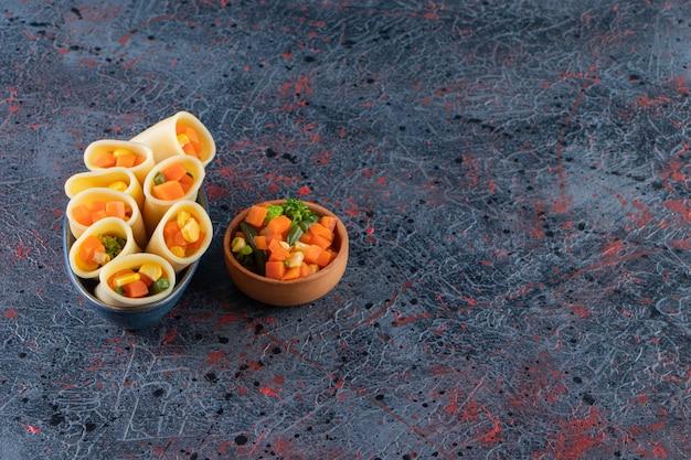 Massa de calamarata recheada com legumes picados numa tigela com mini salada.