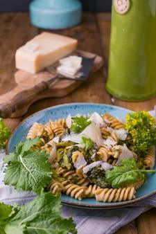 Massa de cime di rapa em um prato com parmesão em uma mesa de madeira. comida tradicional do sul da itália, da apúlia. foto de estilo rústico. copie o espaço