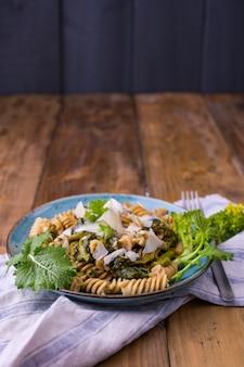 Massa de cime di rapa em um prato com parmesão em uma mesa de madeira. comida tradicional do sul da itália, da apúlia. foto de estilo rústico.