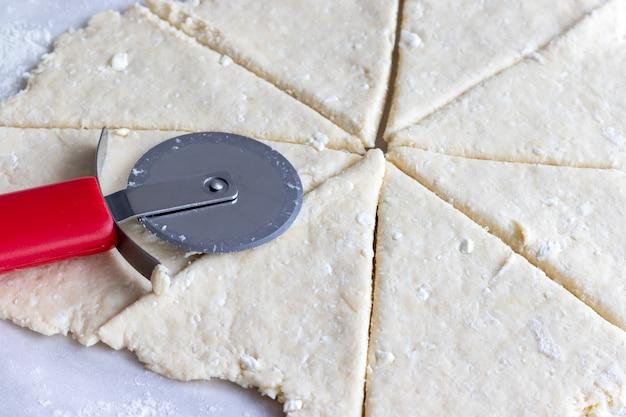 Massa de coalhada crua cortada e enrolada com faca de pizza redonda vermelha em papel manteiga