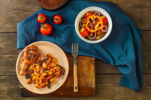 Massa de concha no tomate com coxa de frango assada em uma grelha em um guardanapo azul