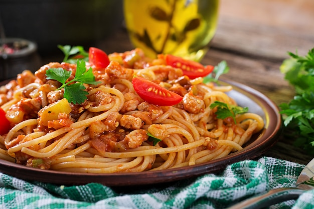 Massa de espaguete à bolonhesa com molho de tomate, legumes e carne picada - massa italiana saudável caseiro em fundo de madeira rústico.