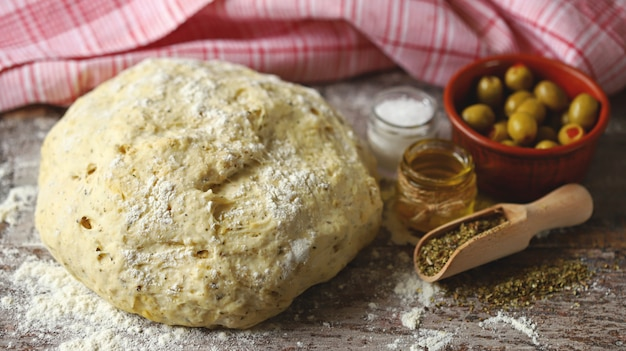 Massa de fermento caseira fresca, azeitonas e especiarias para fazer focaccia com ervas italianas. cozinhando em casa. pão italiano tradicional.