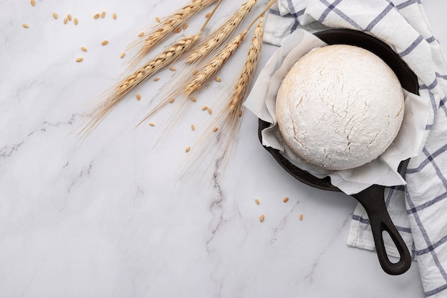 Massa de fermento caseiro crua fresca descansando em frigideira de ferro fundido na mesa de mármore plana leigos.