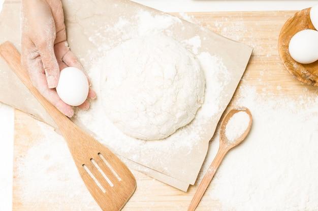 Massa de fermento crua em uma mesa de cozinha enfarinhada, ideia de receita. o conceito de cozinhar em casa ou fazer massa. rolo da massa para massa