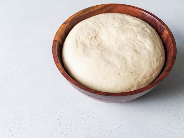 Massa de fermento de farinha de trigo em uma tigela de madeira