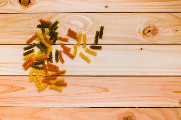 Massa de fusilli tricolor cru para cozinha tradicional italiana na mesa de madeira