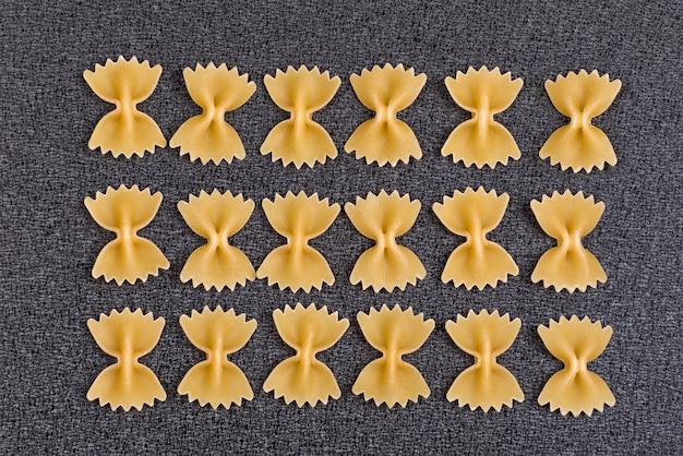 Massa de gravata borboleta no espaço cinza. farfalle não cozido. cozinha nacional italiana. espaço culinário.