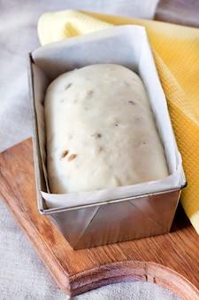 Massa de levedura crua em forma de lata, pronta para assar pão com sementes de girassol