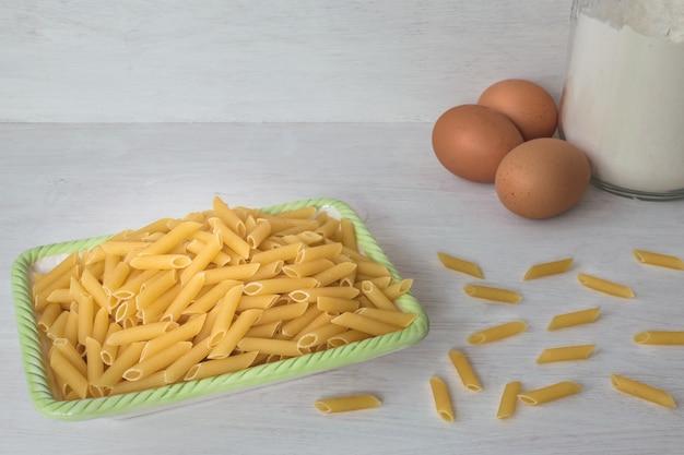 Massa de ovo seco em uma tigela e um grupo de ovos e farinha