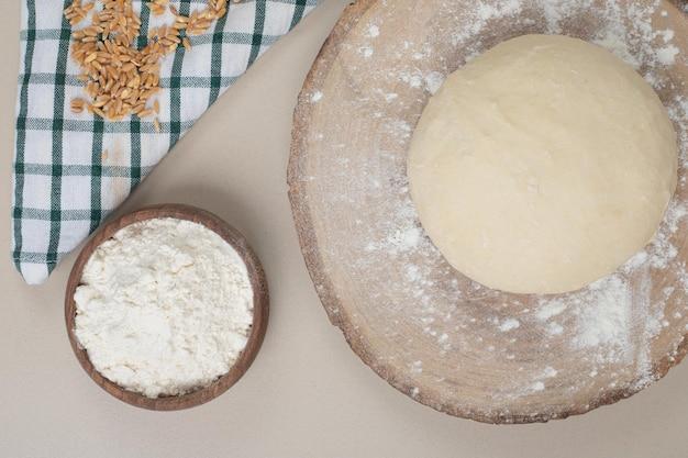 Massa de pão com uma tigela de madeira de farinha na placa de madeira.