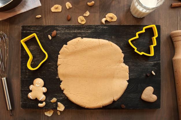 Massa de pão de gengibre com biscoitos e formas culinárias de bota do papai noel e árvore de natal na mesa da cozinha