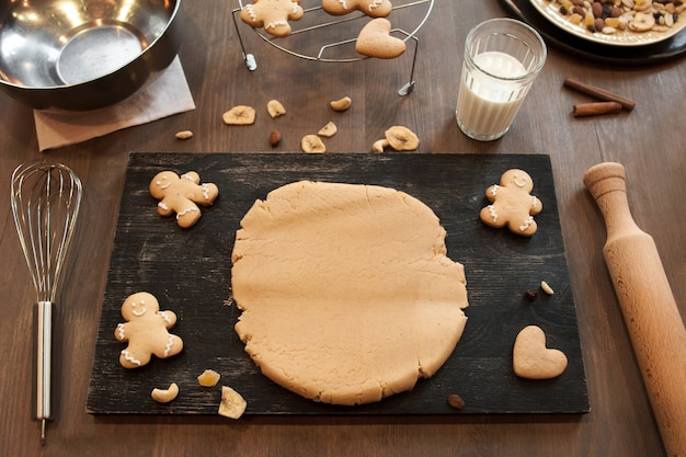 Massa de pão de gengibre e biscoitos na mesa da cozinha