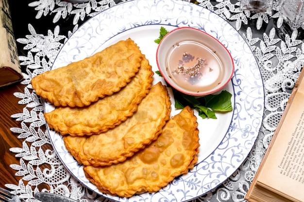 Massa de pão sírio recheada frita servida com molho com gergelim