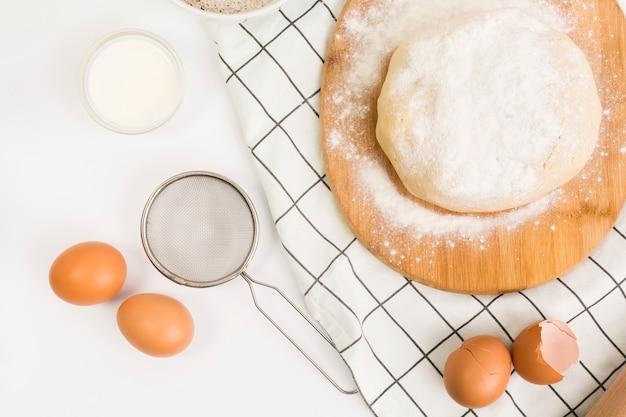 Massa de pastelaria unbaked e ingrediente cru sobre a superfície branca