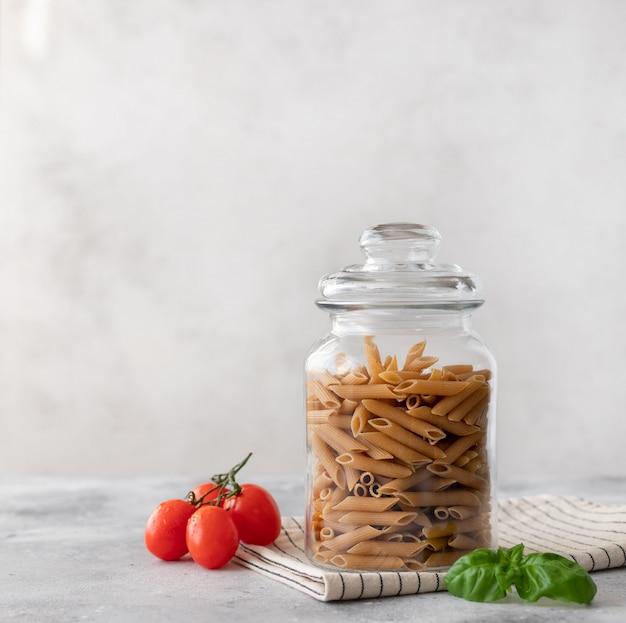 Massa de penne de trigo integral em um recipiente de vidro. fechar-se. conceito de dieta