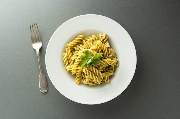 Massa de pesto na placa branca sobre o fundo cinzento, fusili, espaguete. comida italiana.