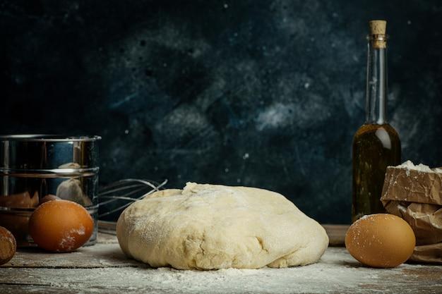 Massa de pizza cozinhar na cozinha de casa. massa caseira para pão, pizza, bolos e pãezinhos. ingredientes de massa sobre um fundo rústico de madeira
