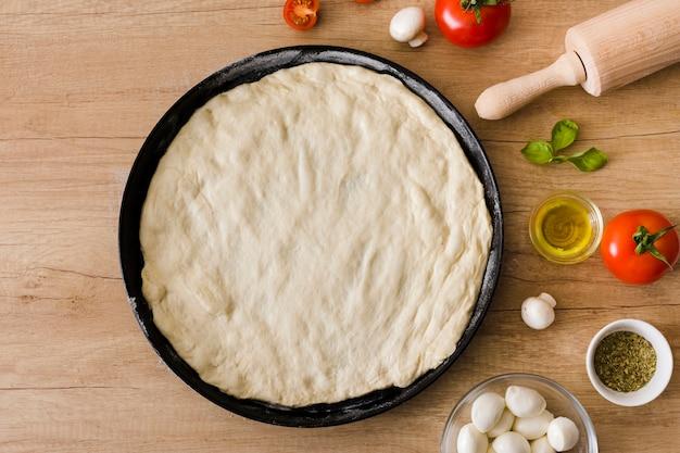 Massa de pizza crua com coberturas e rolo em pano de fundo de madeira
