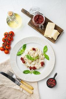 Massa de ravióli com molho de creme de cogumelos e queijo - estilo de comida italiana com parmesão de manjericão e tomate no prato branco, fundo branco, vista superior plana lay