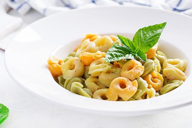 Massa de ravióli italiano com espinafre e ricota em chapa branca. macarrão tortellini italiano.