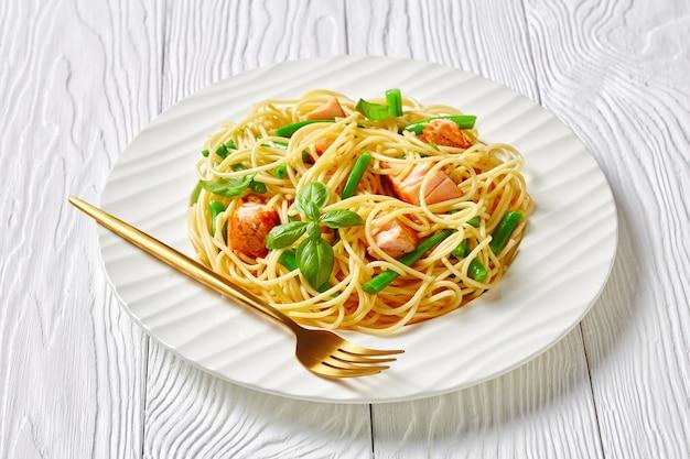 Massa de salmão selvagem com espaguete italiano, feijão verde e molho de manteiga de alho com manjericão fresco por cima servido em um prato branco com garfo em uma mesa de madeira branca, close-up