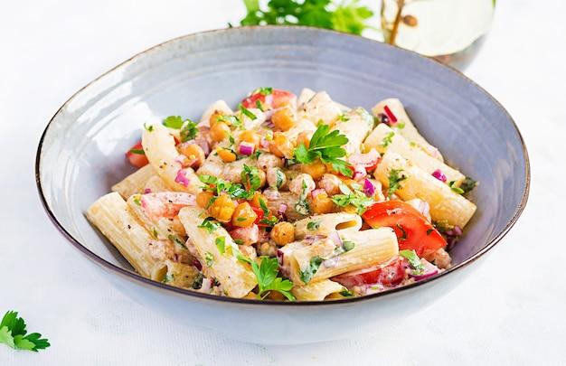Massa de vegetais vegetarianos. macarrão rigatoni com tomate, cebola roxa, salsa e grão de bico frito com molho de nozes. comida vegana.