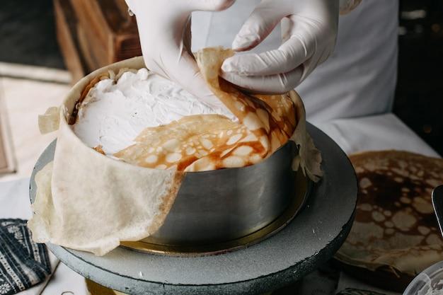 Massa dentro de panela redonda com cozinheiro espalhando creme de leite nele dentro da cozinha