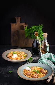 Massa ditalini tradicional italiana com almôndegas em molho de tomate e legumes em uma tigela. massas ditalini e bolinhos de boi com molho de tomate marinara.