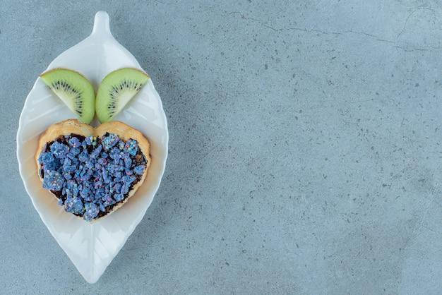 Massa doce em forma de coração com fatias de kiwi.