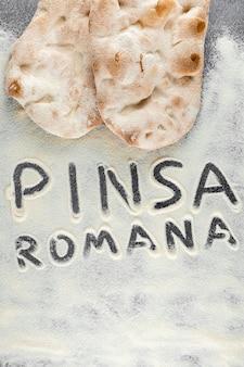 Massa e farinha com texto pinsa romana em fundo preto. cozinha gourmet italiana scrocchiarella. prato tradicional na itália.